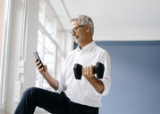 Successful manager using smartphone and training with a dumbbell - KNSF04958