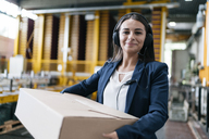 Young woman working at parcel service, carrying parcel in warehouse - KNSF04961