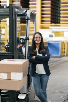 Confident woman standing in logistics center, with arms crossed - KNSF04967