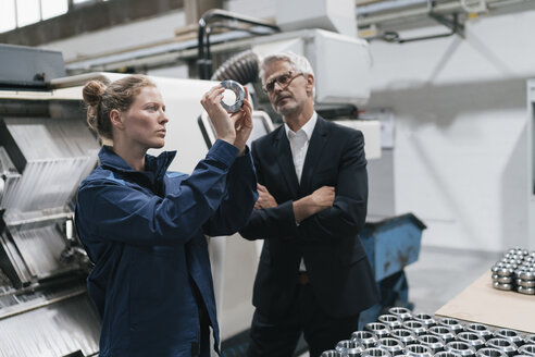 Manager and skilled worker in high tech enterprise, checking machine parts - KNSF04982