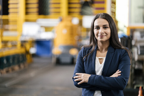 Confident woman standing in logistics center, with arms crossed - KNSF04991