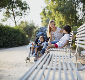 Mother sitting on park bench, talking to one of her sons - AZOF00058