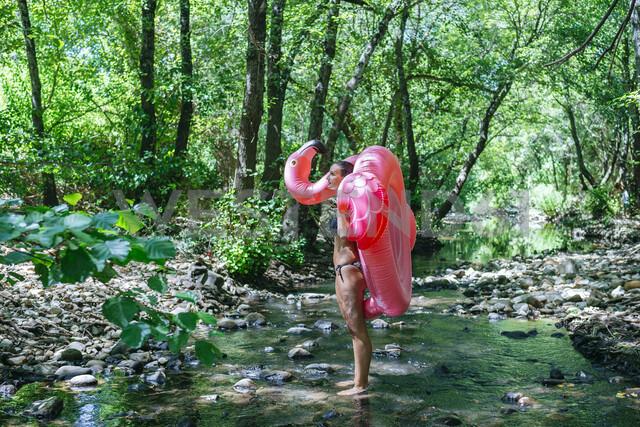 Woman walking in river, carrying an inflatable flamingo - KIJF02019 - Kiko Jimenez/Westend61