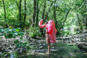 Woman walking in river, carrying an inflatable flamingo - KIJF02019