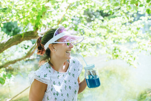Laughing woman drinking blue drink in glass jar - KIJF02022