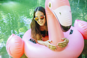Woman floating on water on an inflatable flamingo - KIJF02025