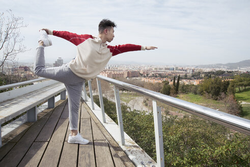 Chinese man doing yoga with cityscape in background, Montjuic Mountain, Barcelona, Spain - AURF06766