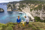 Family on vacations looking at view of coastline with cliffs, Nusa Penida, Bali, Indonesia - AURF06880