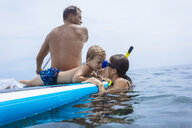 Family on sup surfboard in ocean,Bali,Indonesia - AURF06898