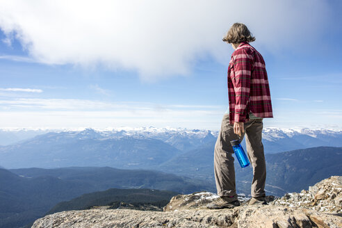 Hiker resting and looking at view while standing at top of Whistler Mountain, Garibaldi Provincial Park, Whistler, British Columbia, Canada - AURF06934