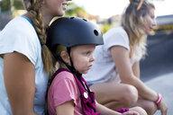 Girl in bicycle helmet sitting on mothers lap, Canggu, Bali, Indonesia - AURF07039