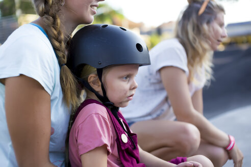 Girl in bicycle helmet sitting on mothers lap, Canggu, Bali, Indonesia - AURF07039