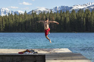 Man in swimming trunks jumping into Annette Lake from jetty, Jasper National Park, Alberta, Canada - AURF07060