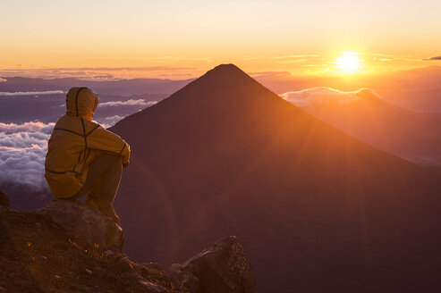 Man looking at view of sunrise from summit of Acatenango Volcano, Guatemala - AURF07096