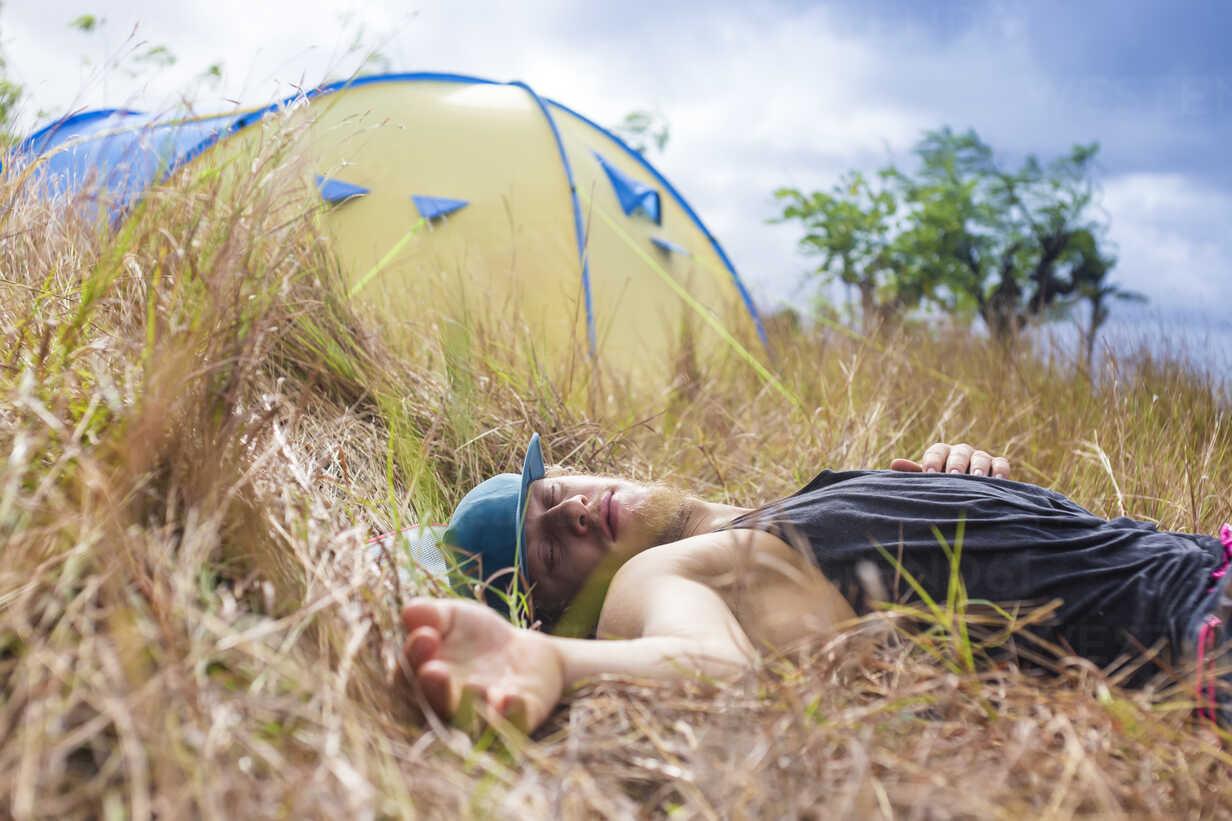 Man sleeping outside tent in meadow, Nusa Penida, Bali, Indonesia - AURF07141 - Cavan Images/Westend61