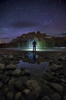 Man standing on lakeshore at night near Castle Mountain, Banff National Park, Alberta, Canada - AURF07153