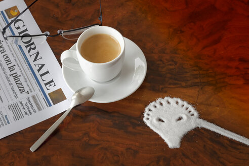 Italy, Venice, newspaper, reading glasses, cup of espresso and sugar shaped like a Venetian mask on table - KLR00708