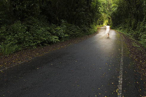 New Zealand, North Island, Egmont National Park, Woman walking on road - MKFF00393