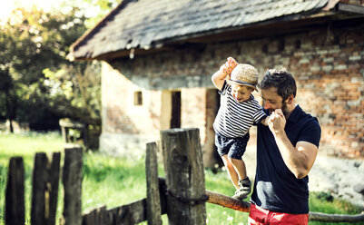 Father assisting his little son in balancing on a fence - HAPF02728