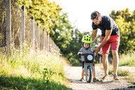 Father teaching little son riding bicycle - HAPF02734