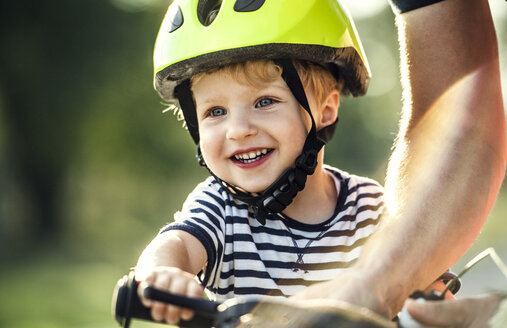 Portrait of smiling toddler wearing cycling helmet - HAPF02737