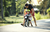 Father teaching little son riding bicycle - HAPF02743