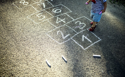 Little girl with drawn hopscotch on the street, partial view - HAPF02746