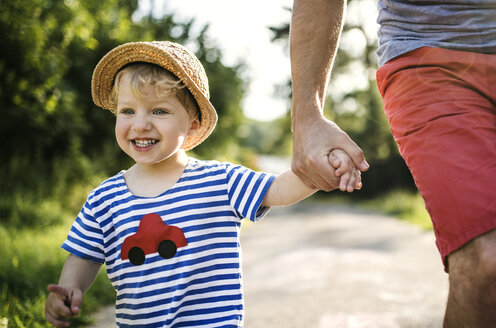 Portrait of laughing toddler walking on father's hand - HAPF02755