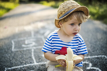 Portrait of toddler boy with banana sitting on the street watching something - HAPF02758
