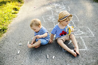 Toddler boy and his little sister sitting together on the street eating bananas - HAPF02764