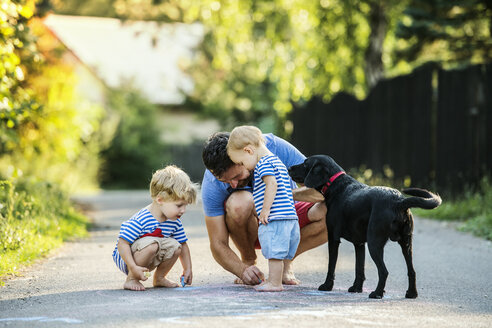 Mature man playing with his little children on the street in summer - HAPF02770