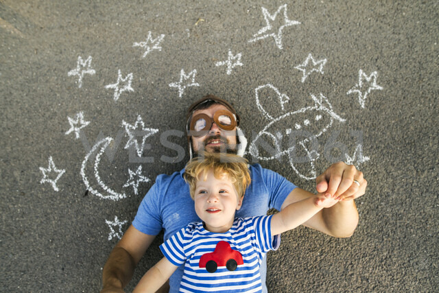 Portrait of mature man wearing pilot hat and his little son lying on asphalt painted with airplane, moon and stars - HAPF02776 - HalfPoint/Westend61