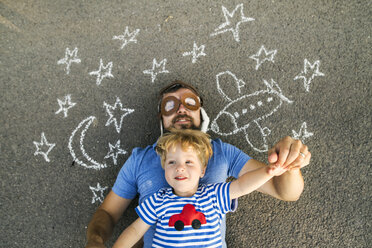 Portrait of mature man wearing pilot hat and his little son lying on asphalt painted with airplane, moon and stars - HAPF02776