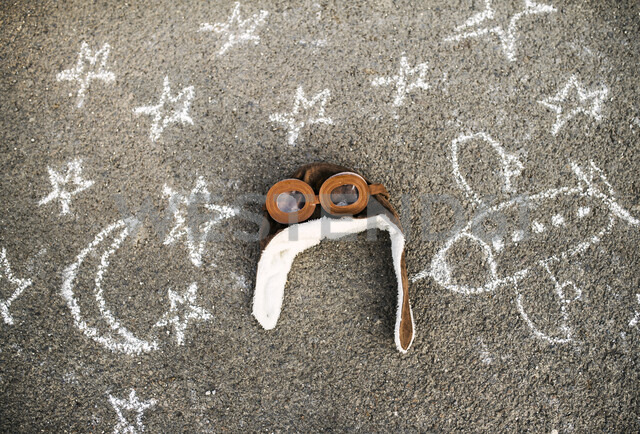 Pilot hat and flying goggles lying on asphalt painted with airplane, moon and stars - HAPF02782