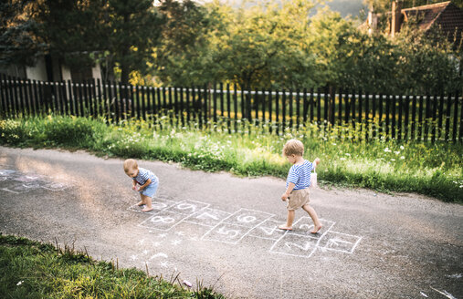 Toddler boy and little sister playing outdoors - HAPF02785