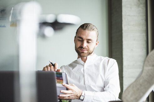 Young businessman sitting in office with feet up using tablet - UUF15177
