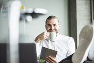 Portrait of smiling businessman in office with tablet and coffee cup - UUF15180
