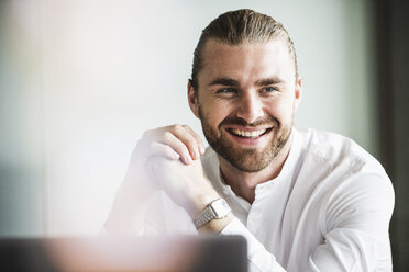 Portrait of smiling young businessman in office - UUF15186