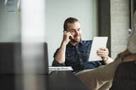 Smiling businessman sitting in office with feet up using tablet - UUF15192