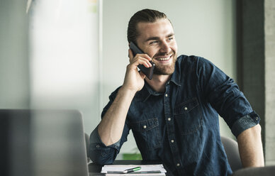 Smiling young businessman on cell phone in office - UUF15201