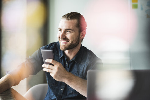 Smiling young businessman in office holding cell phone - UUF15204