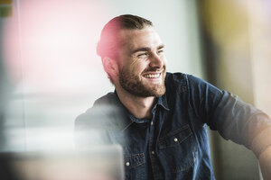 Portrait of smiling young businessman in office - UUF15207