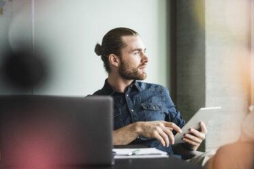 Businessman sitting in office with tablet looking sideways - UUF15210