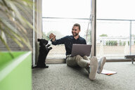 Young businessman with laptop sitting on the floor in office playing with dog - UUF15219