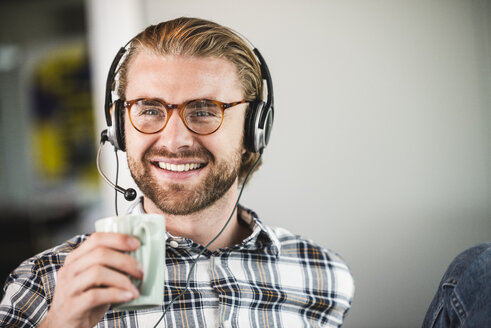 Portrait of smiling casual businessman with cup of coffee and headset - UUF15255