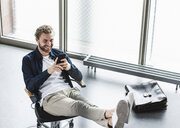 Smiling casual businessman sitting in office with feet up using cell phone - UUF15273