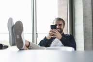 Smiling casual businessman sitting in office with feet up using cell phone - UUF15276