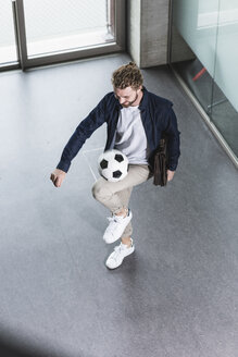 Casual young businessman playing football in office - UUF15279