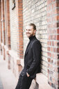 Smiling fashionable young man leaning against brick wall - UUF15294
