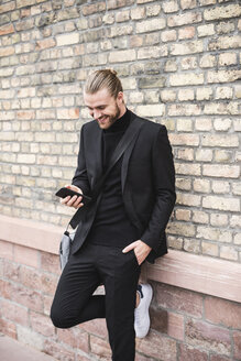 Smiling fashionable young man leaning against brick wall using cell phone - UUF15297